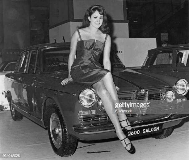 Ann Sidney, winner of the 1964 Miss World contest as Miss United Kingdom, sitting on an Alfa Romeo 2